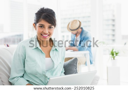 Cheerful businesswoman on couch looking at camera in the office - stock photo