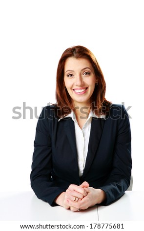Cheerful businesswoman sitting at the table isolated on a white background - stock photo