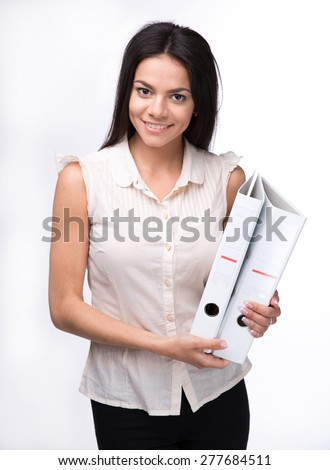 Cheerful businesswoman standing and holding folders over white background. Looking at camera