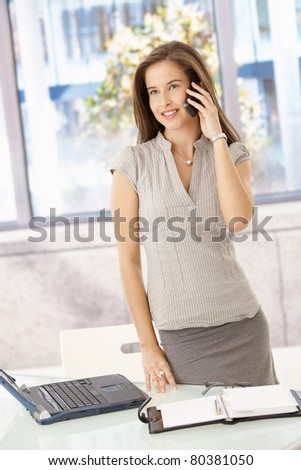 Cheerful businesswoman standing in office, speaking on cellphone, smiling.?