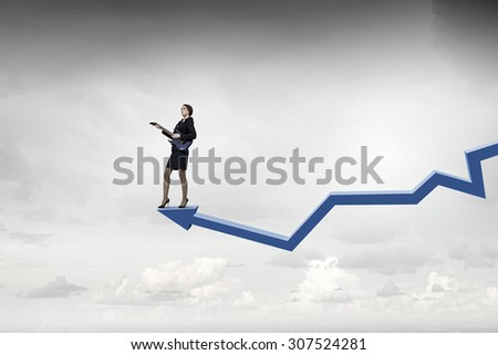 Cheerful businesswoman standing on graph and playing electric guitar - stock photo