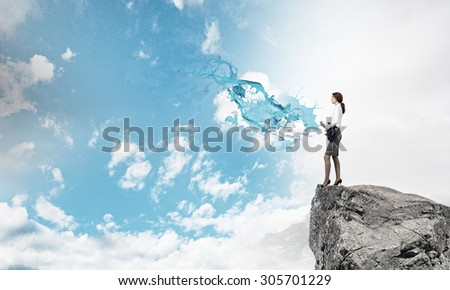 Cheerful businesswoman standing on rock edge and playing electric guitar - stock photo