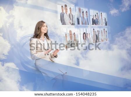Cheerful businesswoman using digital interface while cloud computing - stock photo