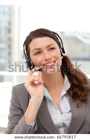 Cheerful businesswoman using earpiece sitting at her desk in her office - stock photo