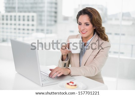 Cheerful businesswoman using laptop at her desk and holding mug in bright office