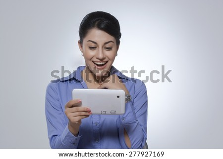 Cheerful businesswoman using tablet computer against gray background - stock photo