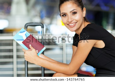 cheerful businesswoman waiting for her flight at airport - stock photo