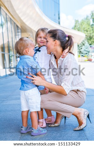 Cheerful businesswoman with her small children - stock photo
