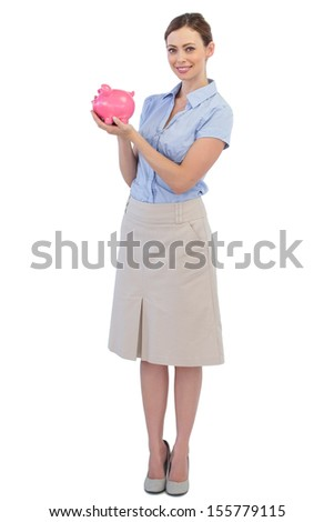 Cheerful businesswoman with piggy bank against white background - stock photo
