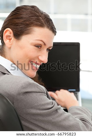 Cheerful businesswoman working on her laptop in her office
