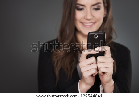 Cheerful businesswoman writing message on mobile phone - stock photo
