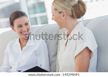 Cheerful businesswomen talking and working together in bright office - stock photo