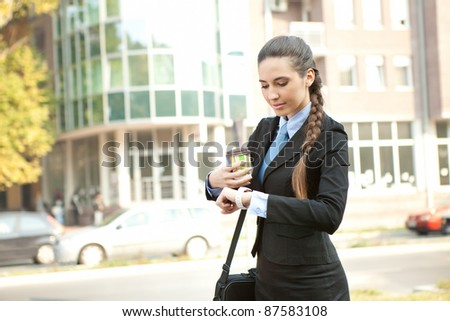 cheerful,  busy businesswoman checking the time, outdoor - stock photo
