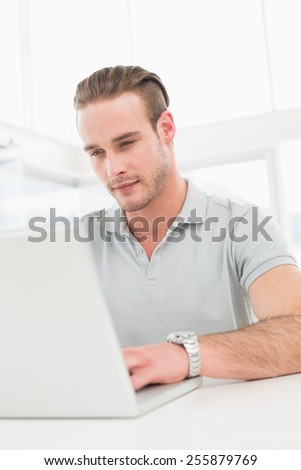 Cheerful casual businessman typing on laptop in his office - stock photo