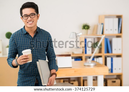 Cheerful casual businessman with coffee and folders in his hands