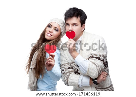 cheerful casual caucasian young couple in winter clothing holding red hearts. isolated on white - stock photo