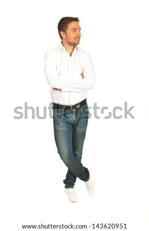 Cheerful casual executive standing with hands and legs crossed and looking away isolated on white background