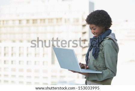 Cheerful casual model using her laptop outdoors on a sunny day - stock photo
