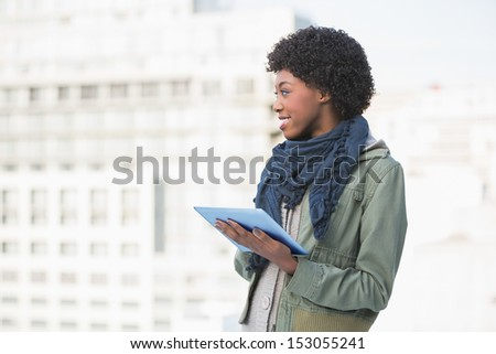 Cheerful casual woman holding tablet pc outdoors on a sunny day