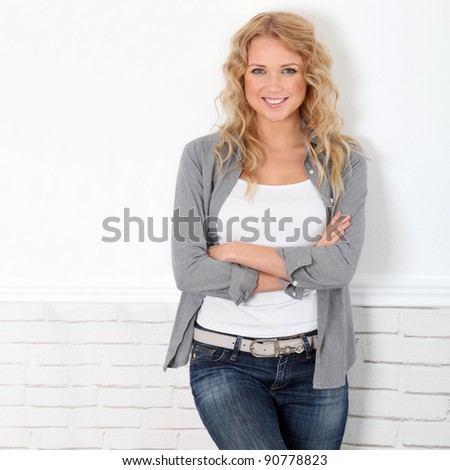 Cheerful casual woman standing on white background - stock photo