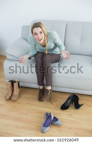 Cheerful casual woman tying her shoelaces sitting on couch looking at camera