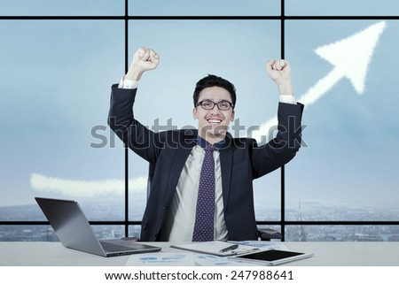 Cheerful caucasian businessman celebrate his success in the office with an upward arrow