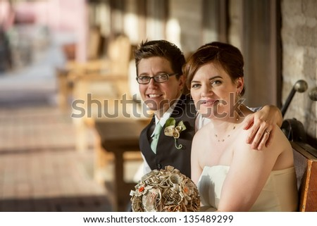 Cheerful Caucasian gay female couple sitting together - stock photo