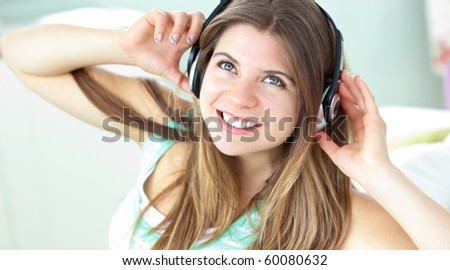 Cheerful caucasian girl listening to music sitting on a sofa at home