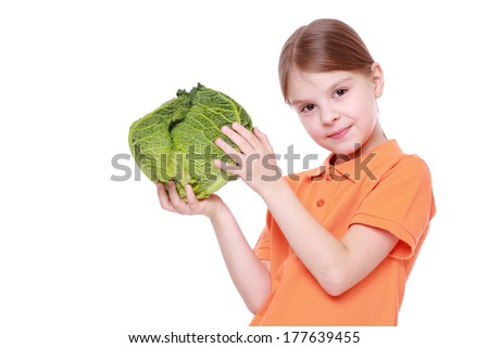 Cheerful caucasian little girl holding a head of cabbage on Food and Drink theme
