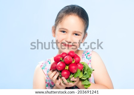 Cheerful caucasian little girl holding a radish - stock photo