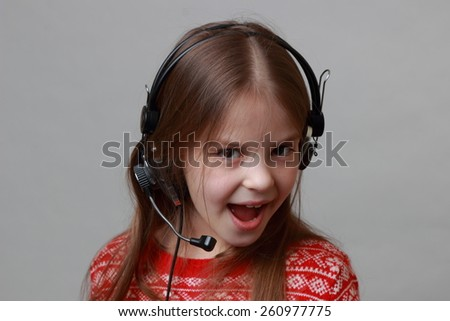 Cheerful caucasian little girl wearing red christmas sweater is singing - stock photo