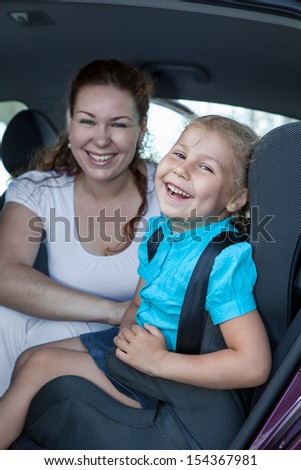 Cheerful Caucasian mother with daughter sitting in car safety seat