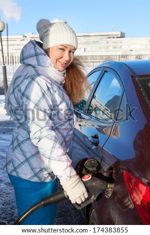 Cheerful Caucasian woman fueling car at winter season - stock photo