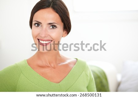 Cheerful caucasian woman with confidence looking at the camera while smiling at indoors - copy space - stock photo