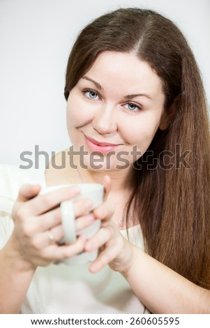 Cheerful Caucasian woman with long hair holding tea mug in hands, grey background - stock photo