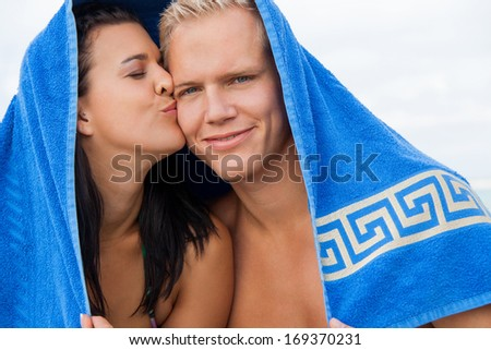 Cheerful Caucasian young happy couple made of a blond handsome man and an attractive brunette woman, with a blue towel covering their heads - stock photo