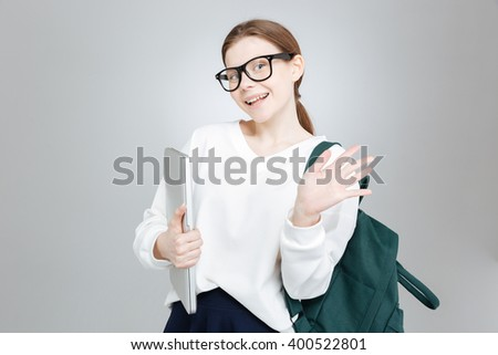 Cheerful charming girl student in glasses with backpack holding laptop and waving with hand  - stock photo
