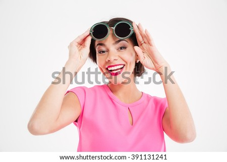 Cheerful charming young woman in sunglasses over white background - stock photo