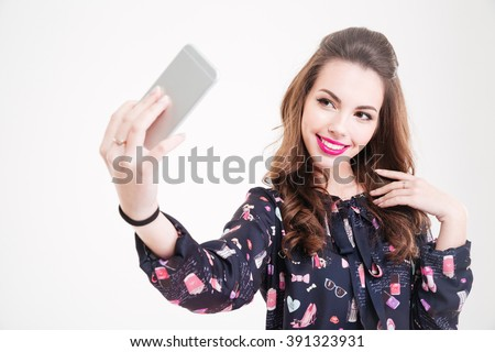 Cheerful charming young woman making selfie using smartphone over white background  - stock photo