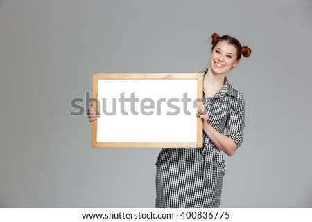 Cheerful charming young woman standing with blank whiteboard over grey background - stock photo