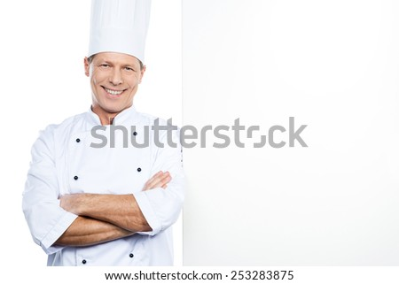 Cheerful chef. Confident mature chef in white uniform leaning at the copy space and smiling while standing against white background - stock photo
