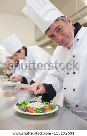 Cheerful Chef's preparing their salads in the kitchen - stock photo