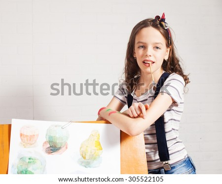 Cheerful child artist. Girl in classroom near easel - stock photo