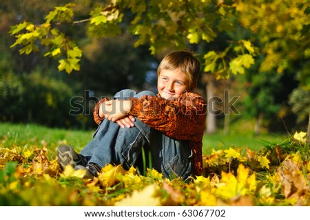 Cheerful child in autum meadow - stock photo