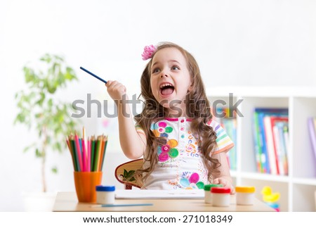 Cheerful child little girl drawing with pencils in preschool - stock photo