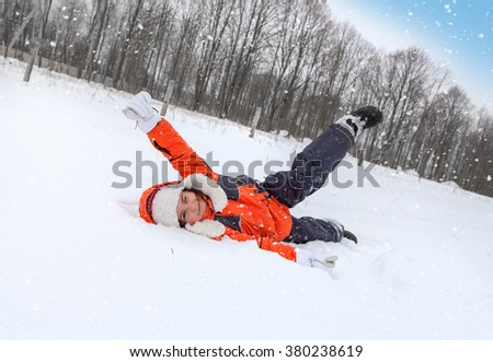 Cheerful Child Tumbles in Snow in Winter
