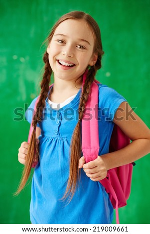 Cheerful child with backpack looking at camera in isolation - stock photo