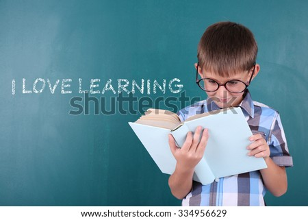 Cheerful child with book at the blackboard. I love learning concept - stock photo