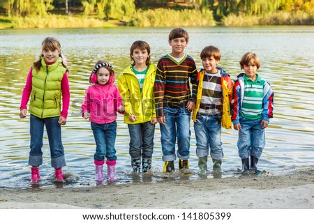 Cheerful children group standing in autumn river - stock photo