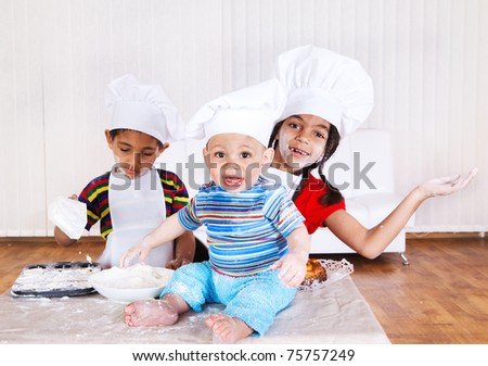 Cheerful children in aprons and hats - stock photo